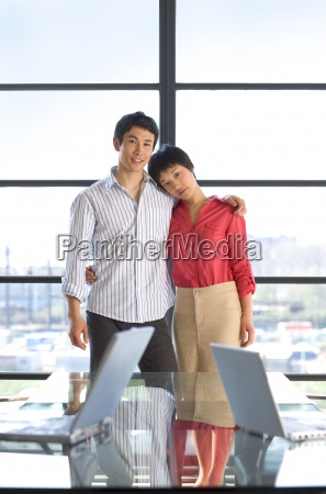 young couple embracing by window smiling