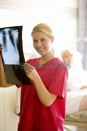 female nurse holding up x ray