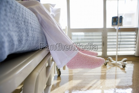 patientinnen mit rosa hausschuhen auf krankenhausbett