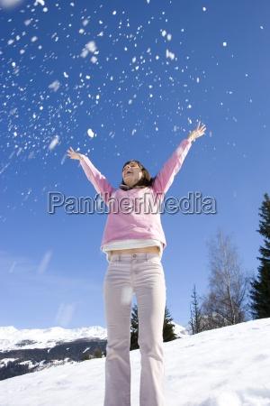 junge frau werfen schnee in luft