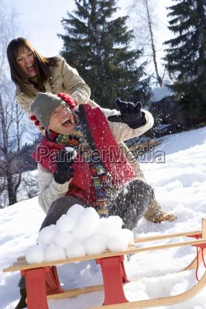 junge paare die schneeballschlacht schneeball stapel
