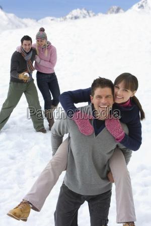 two young couples in snow field