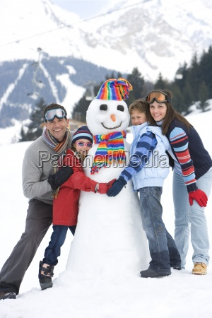 family of four embracing snowman in