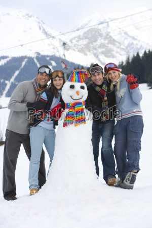 two young couples standing by snowman