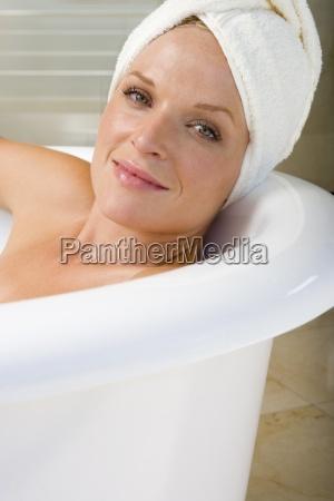 young woman lying in bath towel