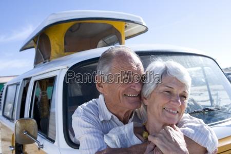 senior couple embracing by camper van
