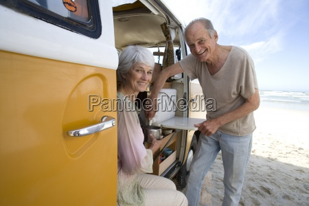 senior couple making tea in camper