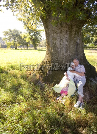 senior couple reclining against tree in