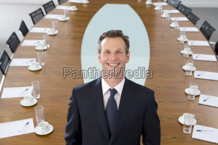 businessman standing at head of conference
