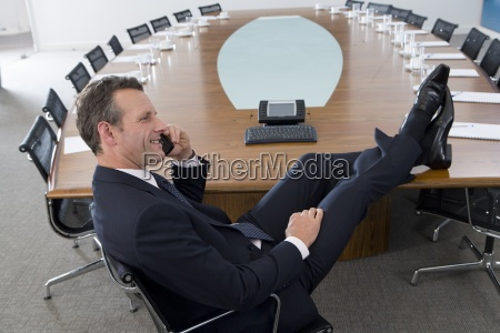 businessman with feet up using telephone
