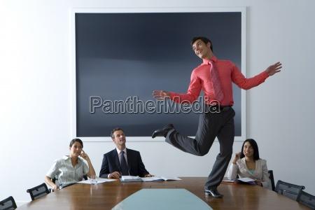 businessman and women watching colleague dancing
