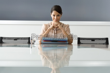 businesswoman with files at boardroom table
