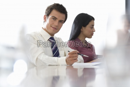 businessman and woman at board table