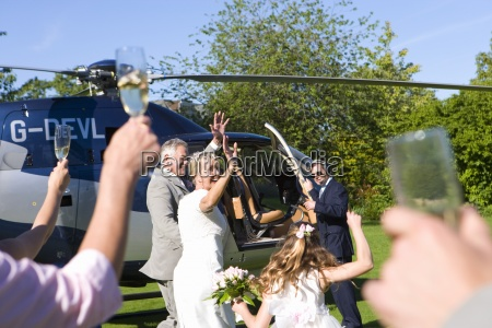 bride and groom by helicopter waving