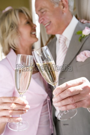 senior bride and groom toasting with