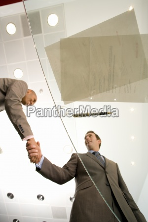 two businessmen shaking hands by paperwork