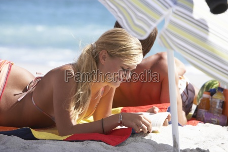 young couple relaxing beneath sunshade on