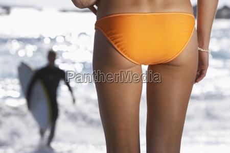 young woman in orange bikini watching