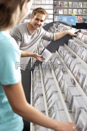 young man showing woman cd in