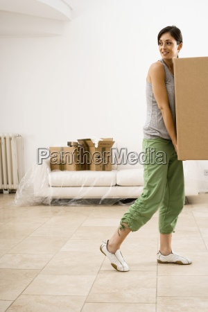 woman moving house carrying large cardboard