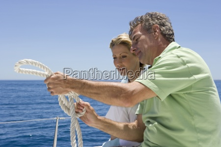 man showing woman how to tie