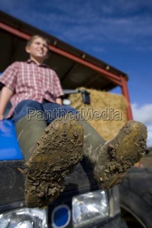 ninyo sentado en el tractor con