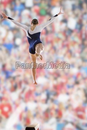 female gymnast jumping on balance beam