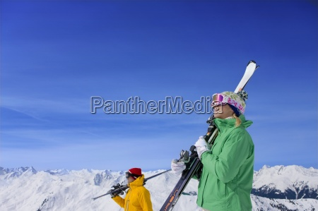 couple wearing goggles and holding skis