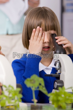 school girl looking into microscopes in