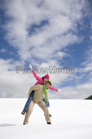 man gibt freundin huckepack durch schnee