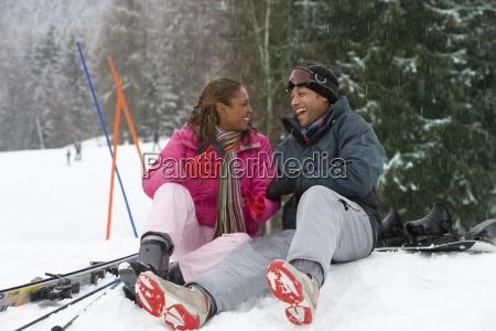 gemischtes rennpaar sitzt im schnee auf