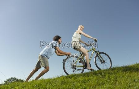 eine frau auf einem fahrrad drueckt