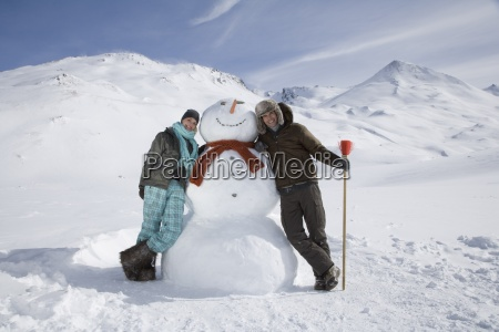 portrait of young couple with snowman