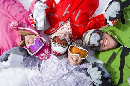 laechelnde familie die im schnee zusammen