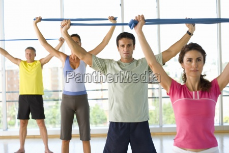 people taking exercise class holding exercise