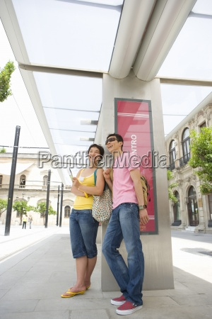 couple leaning against wall at station