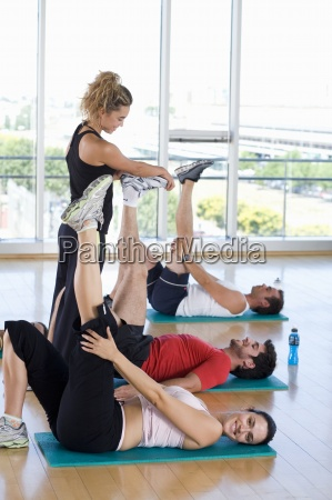female fitness instructor teaching class in