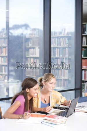 female students studying with laptop computer