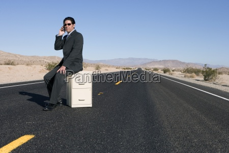 businessman on filing cabinet in middle