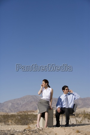 businessman and woman in desert using