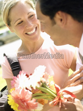 man giving woman bunch of flowers