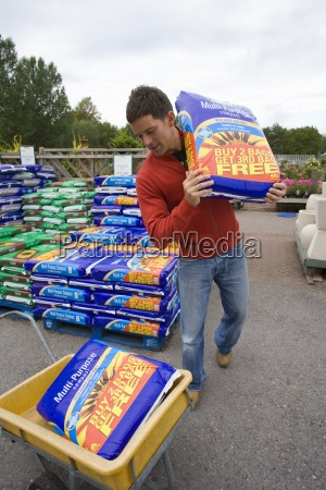 man in garden shop with bag
