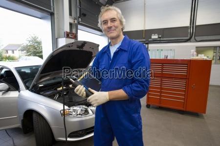 mechaniker mit elektronischen diagnose geraet mit