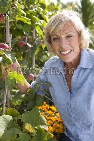 senior woman in orchard smiling portrait