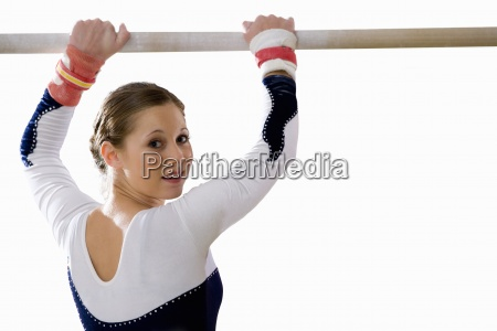 female gymnast with hands on bar
