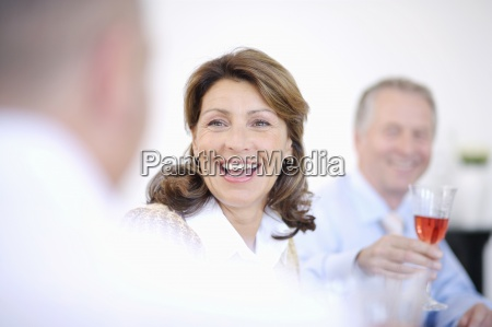 mature woman talking with people at