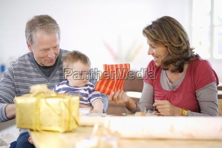 grosseltern mit enkel verpackung praesentiert zusammen