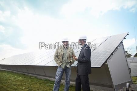 aeltere geschaeftsleute sprechen vor der solarverkleidung