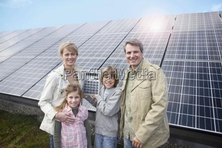 glueckliche familie stand vor der solarpanele