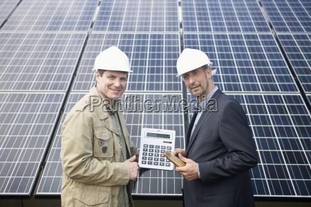 mature businessmen holding a calculator in